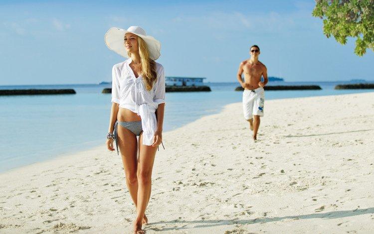 Девушка и парень прогуливаются по пляжу