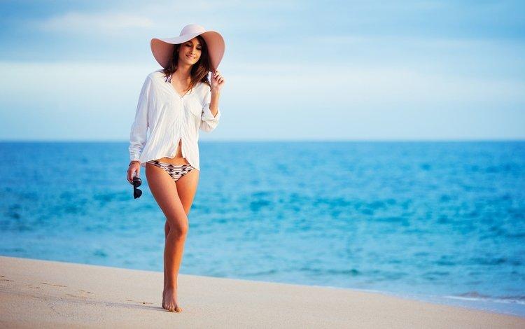 Красивая девушка в шляпе идет по пляжу