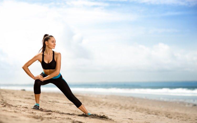 Девушка занимается спортом на пляже