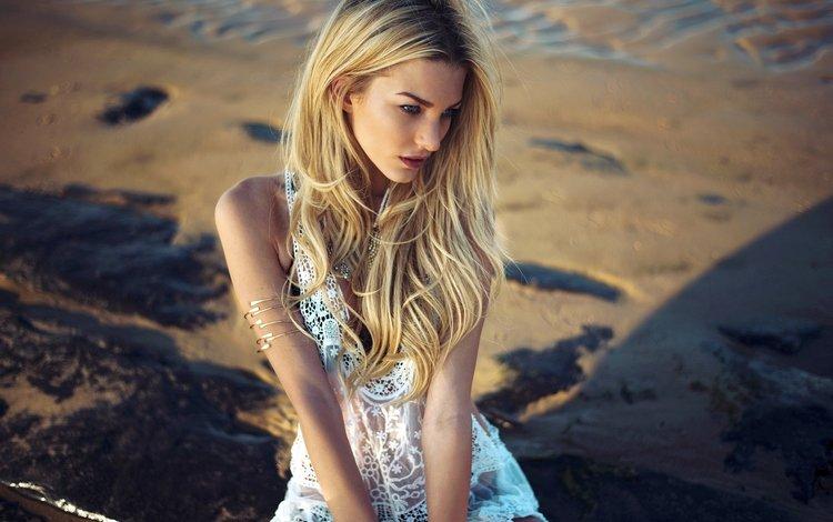 Блондинка сидит на песочном пляже