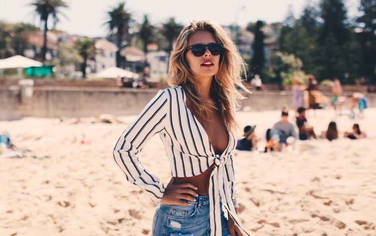 Красивая девушка в полосатой рубашке на пляже