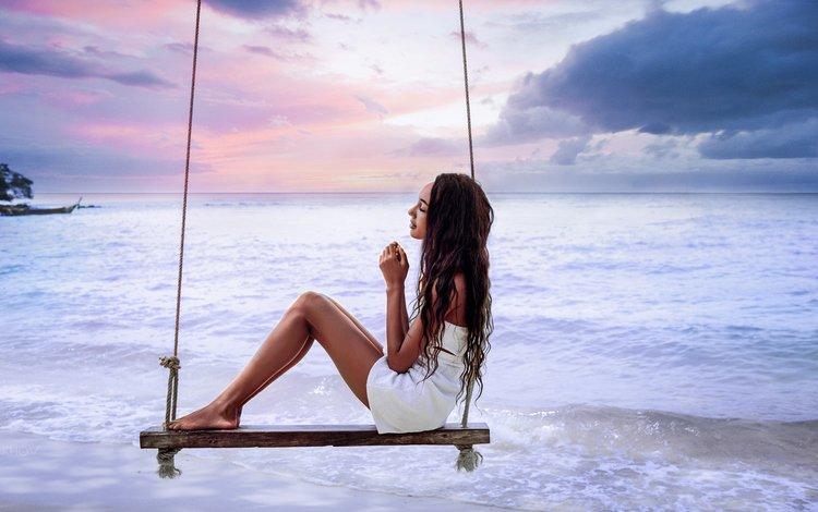 Девушка на качели на берегу