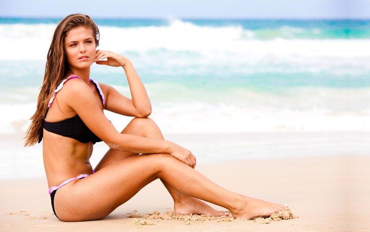 Красивая брюнетка сидит на берегу