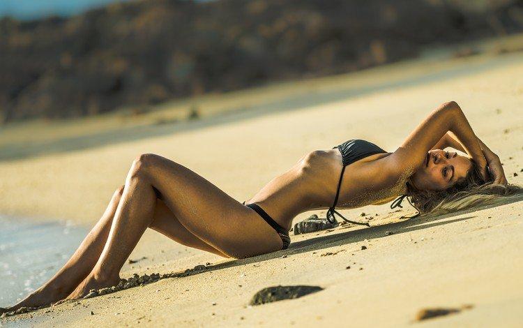 Девушка в черном бикини лежит на берегу моря