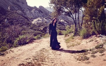 road, trees, mountains, stones, dress, brunette, the bushes, valley, hairstyle, figure, posing, in black, nature, sunny, lana del rey