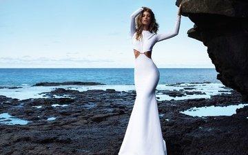 камни, берег, девушка, море, поза, блондинка, взгляд, модель, браслет, секси, красотка, белое платье, кармелла роуз