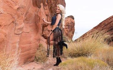 трава, горы, девушка, блондинка, улыбка, юбка, модель, кудри, волосы, браслет, каблуки, фигура, сапоги, стоит, шикарная