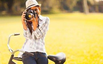 зелень, девушка, улыбка, фотоаппарат, джинсы, шляпа, велосипед, рубашка, шатенка
