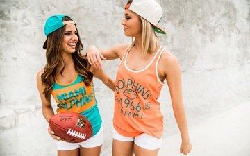 блондинка, улыбка, брюнетка, девушки, мяч, регби, шорты, бейсболка