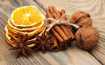 nuts, cinnamon, lemons, spices, star anise, wooden surface