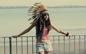 girl, sea, pose, beach, look, the fence, face, feathers, shorts, headdress