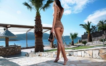 the sky, clouds, girl, sea, brunette, ass, palm trees, model, resort, posing, veranda, long hair, barefoot, mini dress